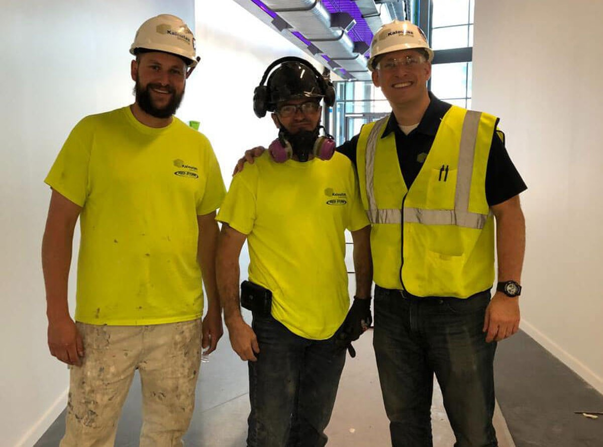 Kaloutas contractors in masks at a job site The Benefits of Going With One Contractor For Multiple Projects