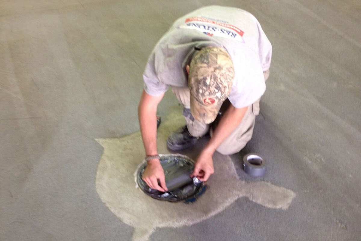 Contractor repairing cracks in an industrial floor How to Fix Cracks and Surface Unevenness on Industrial Floors
